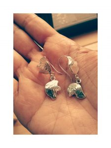 The image is of a hand holding a pair of mulberry leaves earrings.  The earrings are made of textured silver.  The earrings are inspired by an ancient Mulberry tree which is based at Hogarth House in West London.